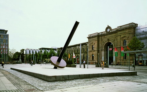 <i>Erdachse M. 1:1000000</i>,       1997<br />      granite,        1765 x 1051 cm (stage), 1271 cm length (pillar), 30 x Ø 250 cm (plate)<br />      Installation view station square Magdeburg, Germany, 1997