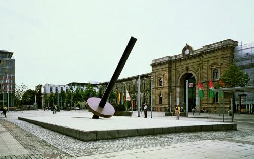 »Erdachse M. 1:1000000«,       1997<br />      granite,        1765 x 1051 cm (stage), 1271 cm length (pillar), 30 x Ø 250 cm (plate)<br />      Installation view station square Magdeburg, Germany, 1997