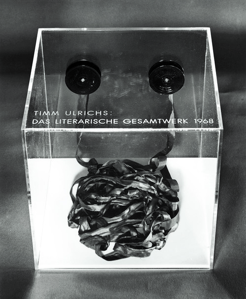 <i>Das literarische Gesamtwerk 1968, Band I</i>,       1968<br />      typewriter tape, acrylglas case,        1.3 x 1000 cm (tape), 25 x 25 x 25 cm (case)<br />