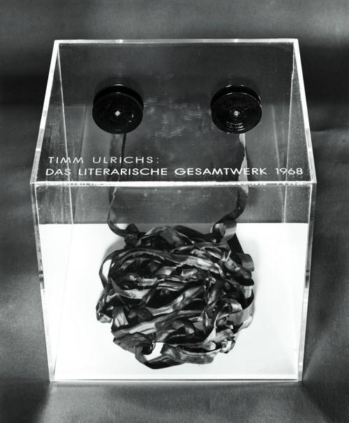 »Das literarische Gesamtwerk 1968, Band I«,       1968<br />      typewriter tape, acrylglas case,        1.3 x 1000 cm (tape), 25 x 25 x 25 cm (case)<br />