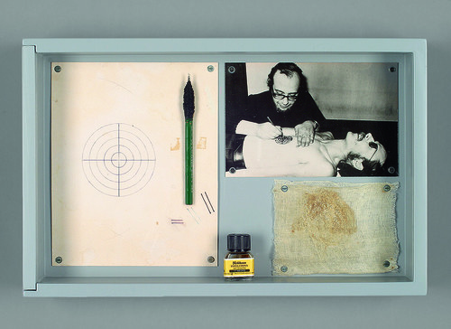 <i>Timm Ulrichs als menschliche Zielscheibe /Timm Ulrichs as a human target</i>,       1971/1974<br />      tattooing performance and documentation material, wooden case, acrylglass window, paper, ink, tattooing needle, black white photography, muslin bandage,        25.5 x 40 x 7 cm<br />