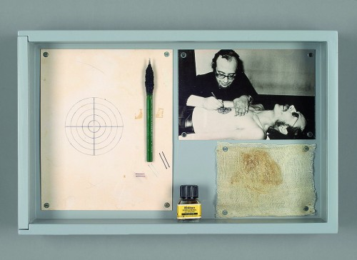 »Timm Ulrichs als menschliche Zielscheibe /Timm Ulrichs as a human target«,       1971/1974<br />      tattooing performance and documentation material, wooden case, acrylglass window, paper, ink, tattooing needle, black white photography, muslin bandage,        25.5 x 40 x 7 cm<br />